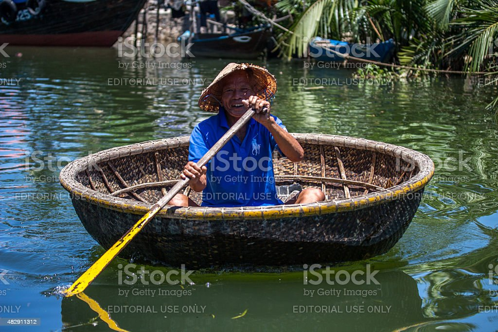 Hoi An,Vietnam-June 18,2015:Vietnamese man in basket boat paddling stock photo
