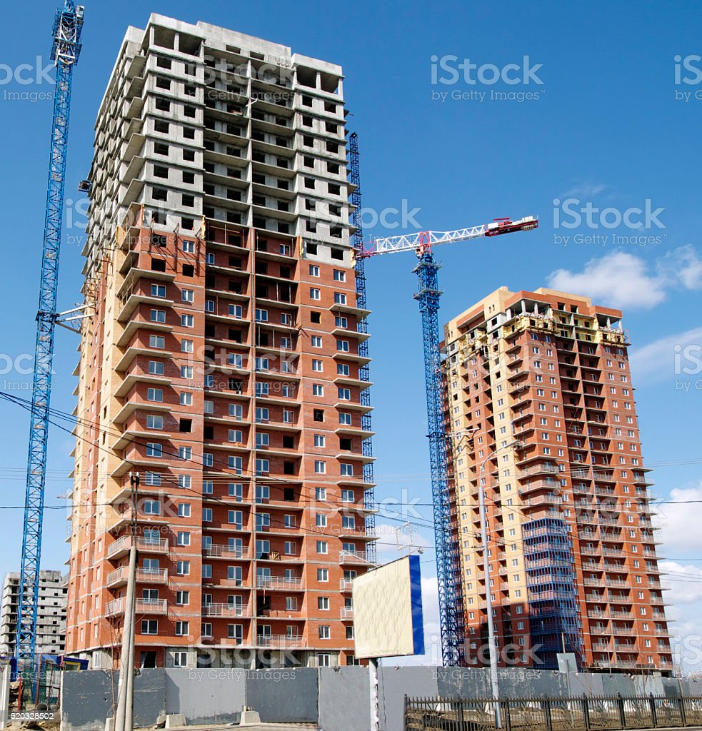 Hoisting crane and house construction stock photo