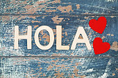 Hola (Hello in Spanish) written with wooden letters, red hearts