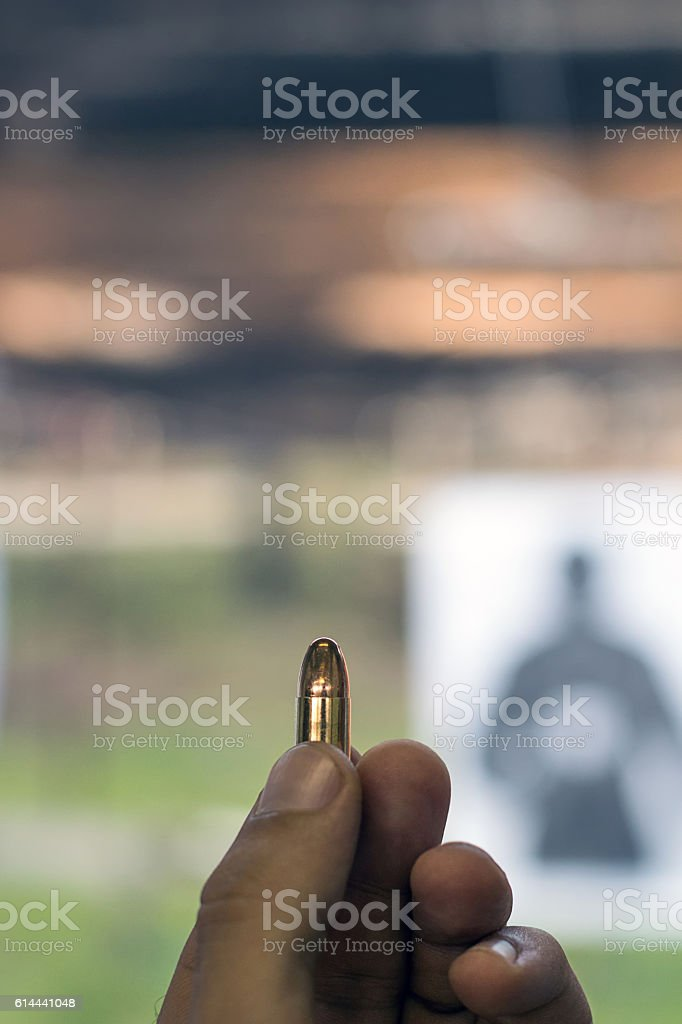 Holding 9mm bullet in hand stock photo