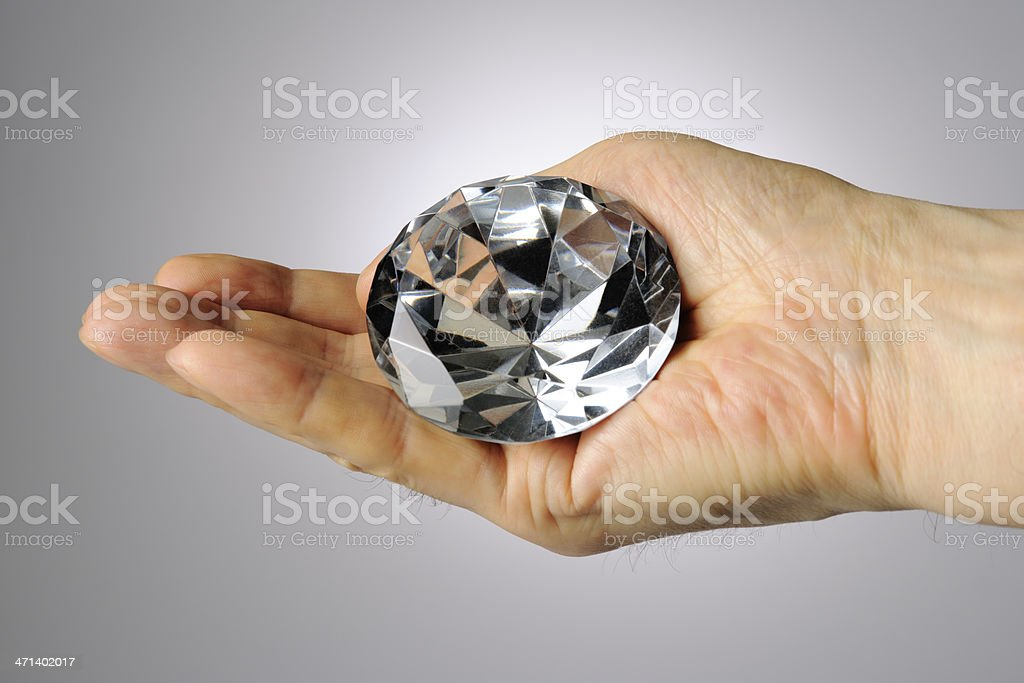 Holding a big diamond against gray gradation background stock photo