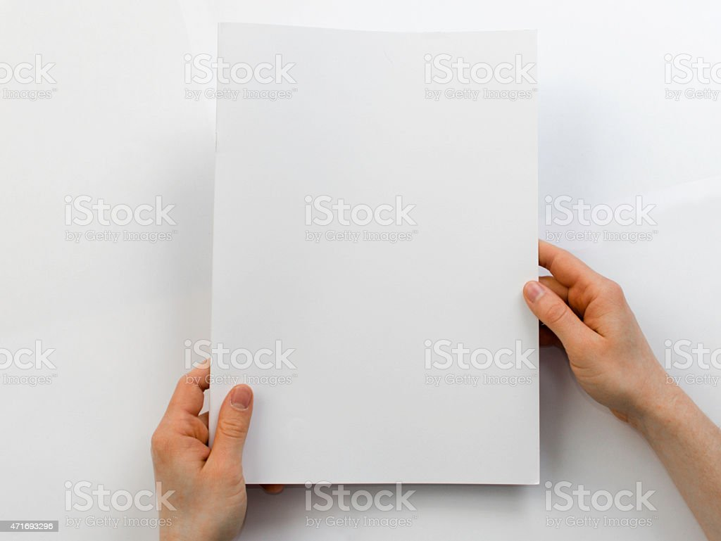 Holding a blank brochure in front of a white background stock photo