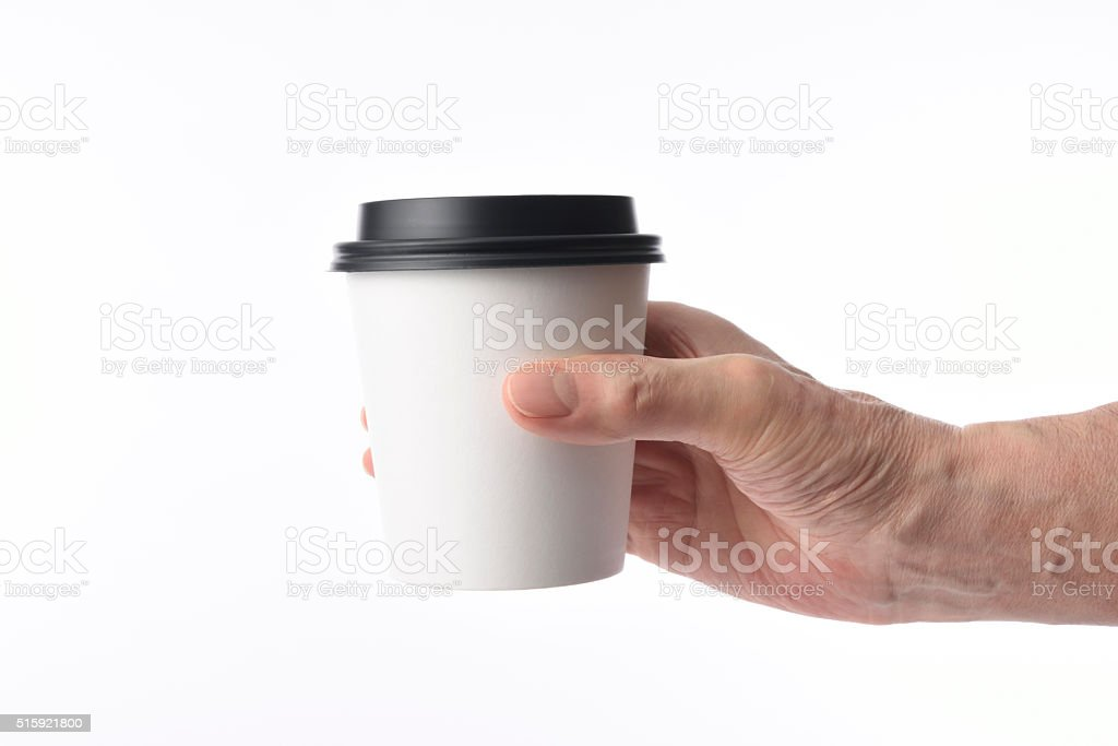 Holding a blank disposable paper coffee cup against white background stock photo