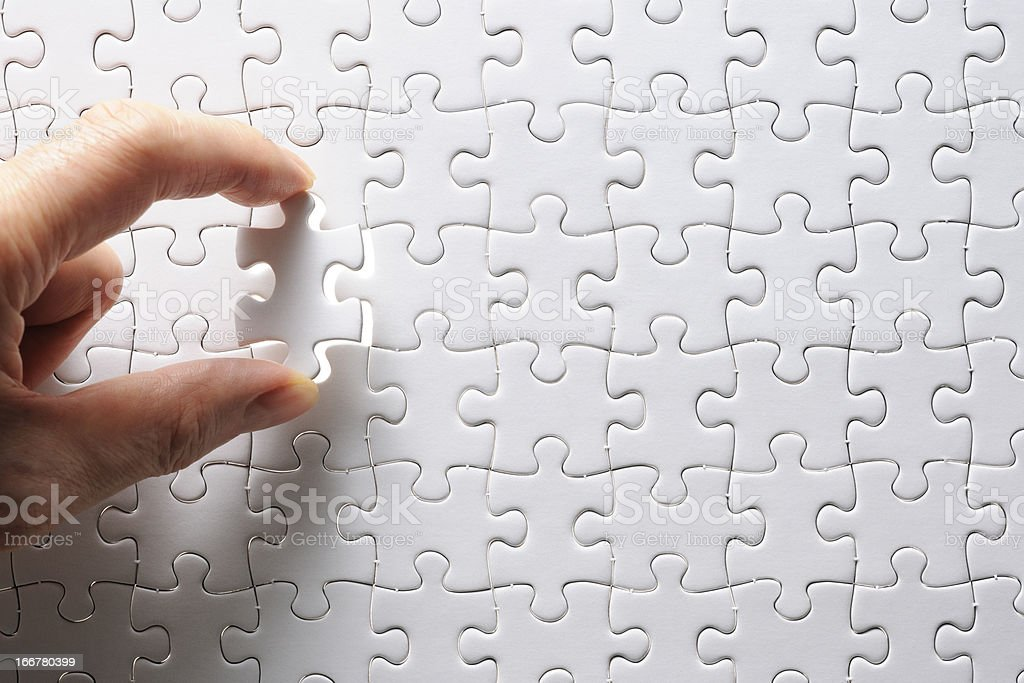 Holding a blank final piece of the jigsaw stock photo