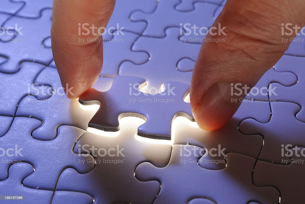 Holding a blue final piece of the jigsaw stock photo