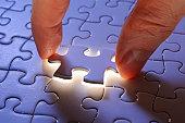 Holding a blue final piece of the jigsaw