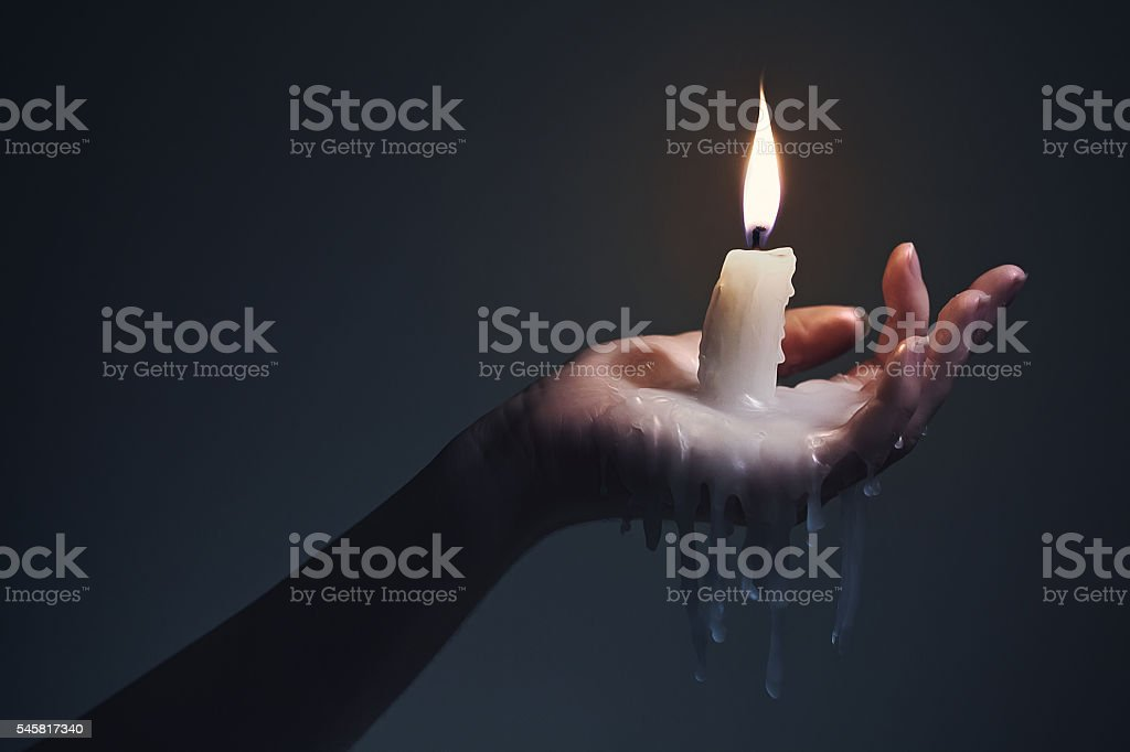 Holding a candle on a dark background. stock photo