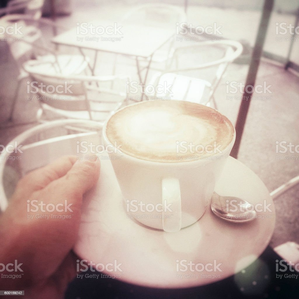holding a cappuccino at the bar outside pov stock photo