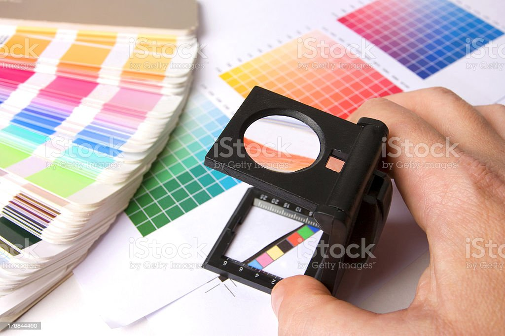 Holding a lupe and examing colours stock photo