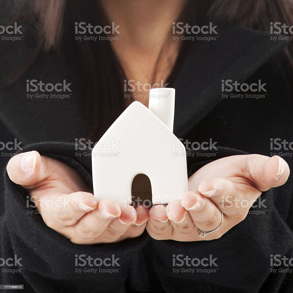 Holding a miniature house stock photo