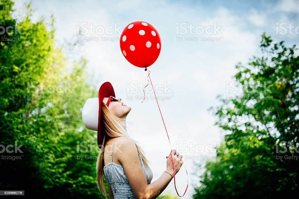 Holding a red balloon stock photo