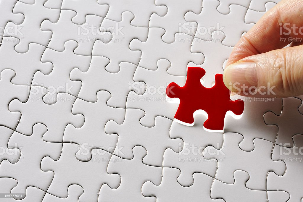 Holding a red final piece of the jigsaw royalty-free stock photo