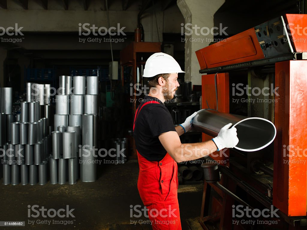 holding a silver manufactured metal tube, stock photo