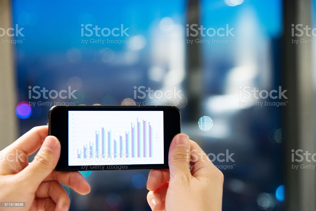 Holding a smart phone with business chart - Stock Image stock photo