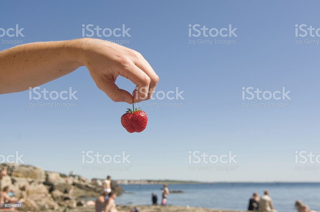 Holding a strawberry at the beach royalty-free stock photo