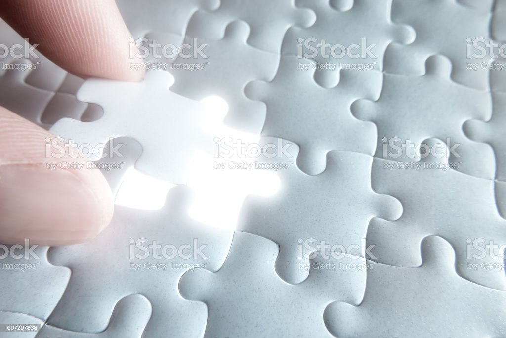 Holding a white blank final piece of the jigsaw stock photo