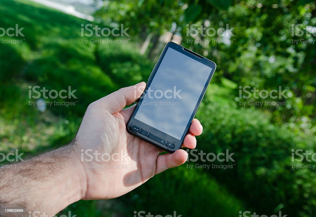 Holding a white mobile phone outdoors royalty-free stock photo