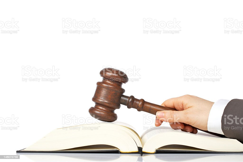 Holding a wooden gavel over the law book royalty-free stock photo