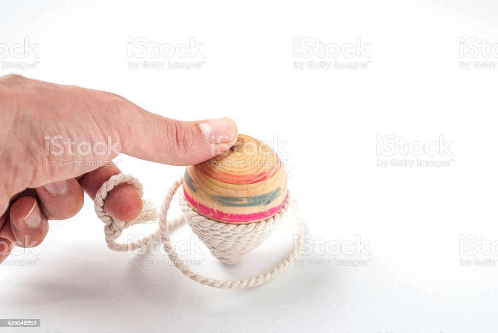 Holding a Wooden Pegtop on a White background stock photo