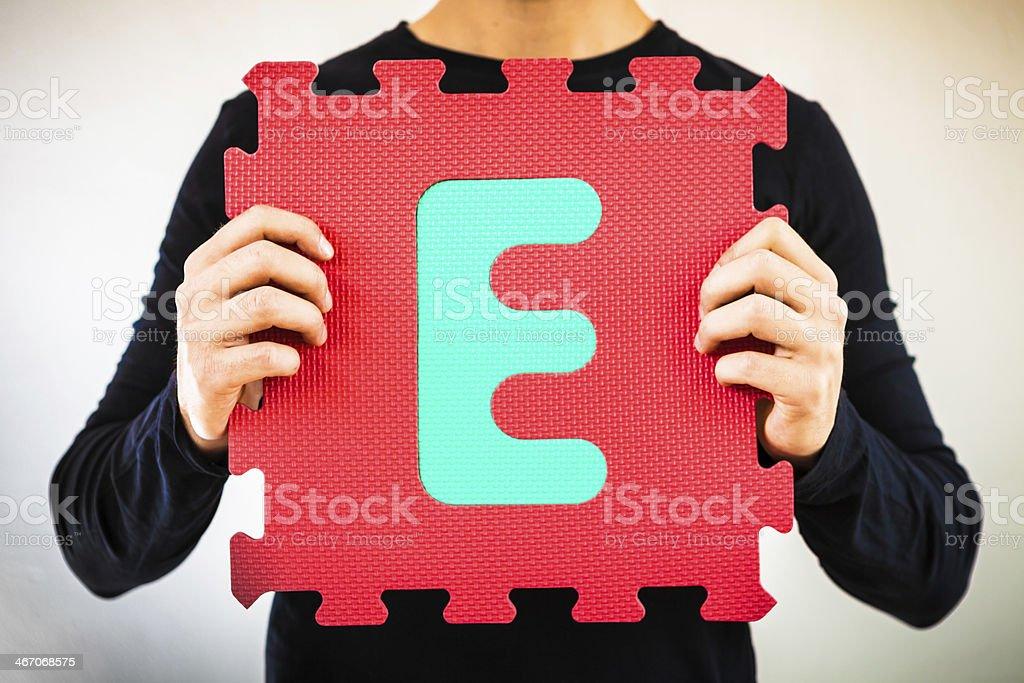Holding Alphabet Puzzle, Letter E royalty-free stock photo