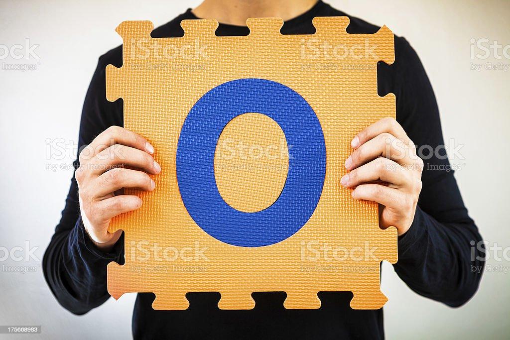 Holding Alphabet Puzzle, Letter O royalty-free stock photo