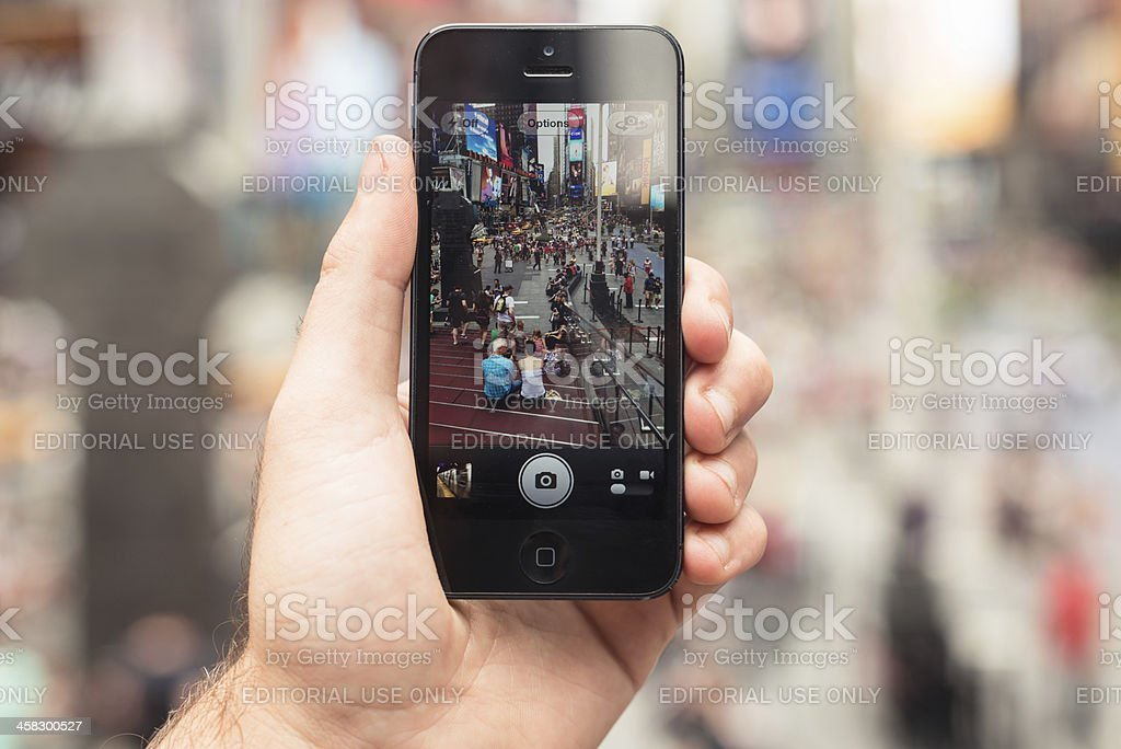 holding an Apple iPhone 5 on Times Square stock photo