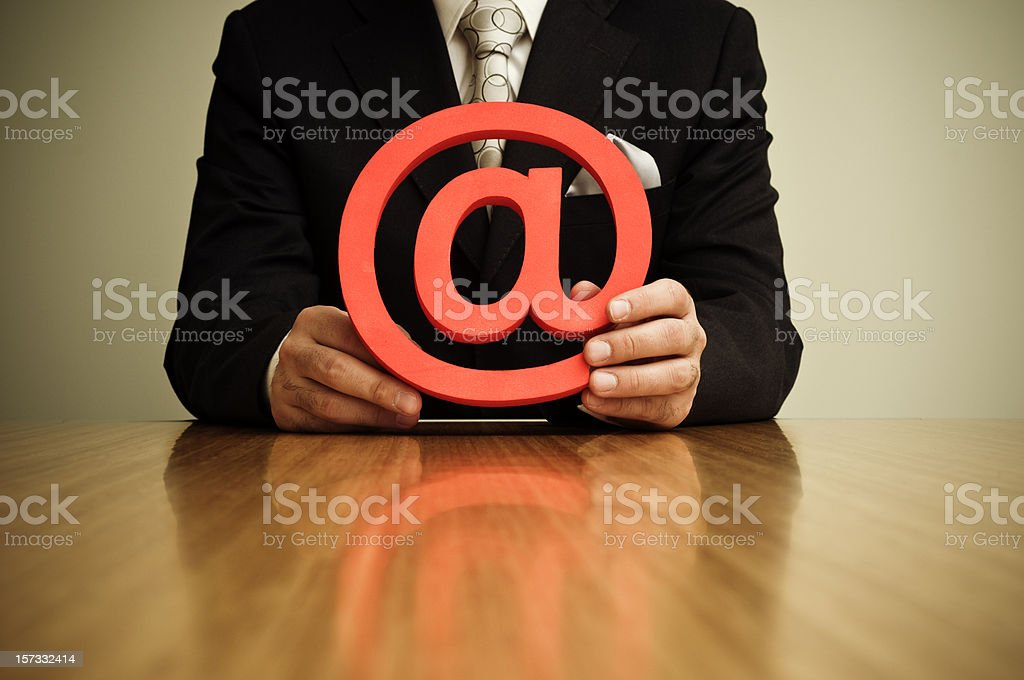 Holding an 'at' symbol stock photo