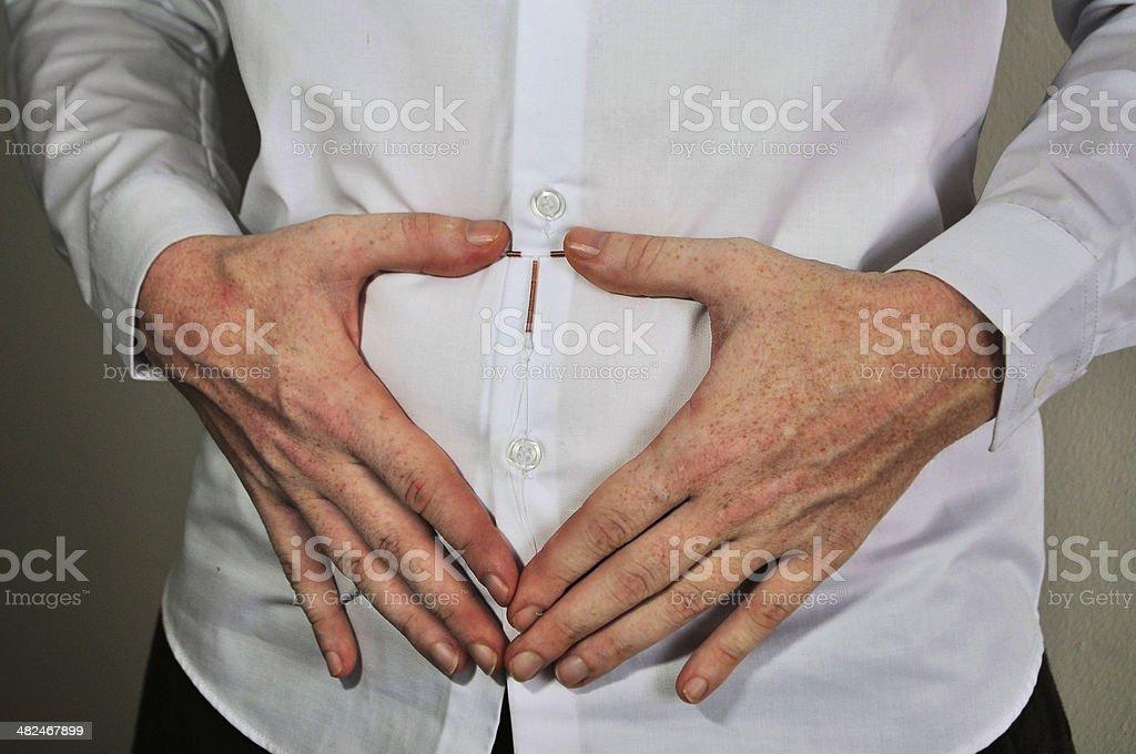 Holding an IUD birth control device over uterus stock photo