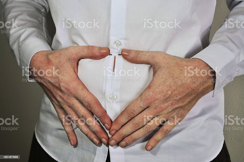Holding an IUD birth control device over uterus stock photo