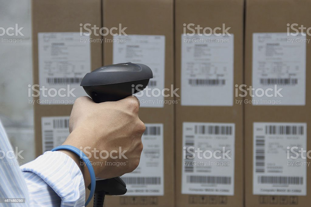 Holding barcode scanner with a label on the boxes stock photo
