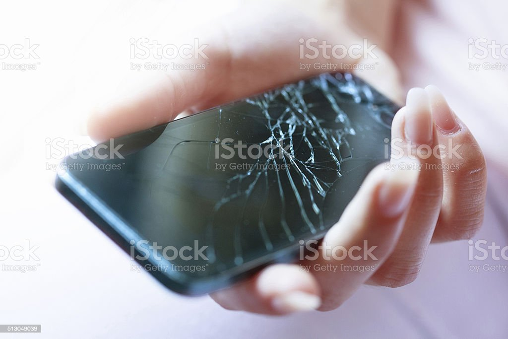 Holding black broken smart phone stock photo