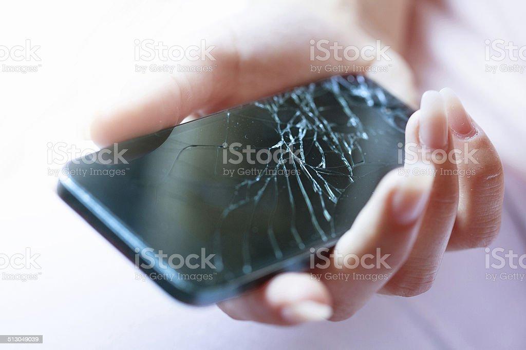 Holding black broken smart phone stock photo