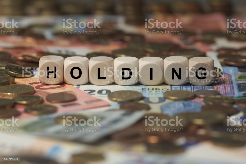 holding - cube with letters, money sector terms - sign with wooden cubes stock photo