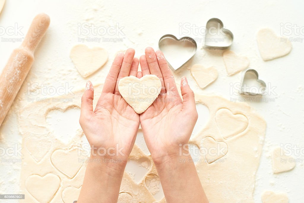 Holding dough heart stock photo