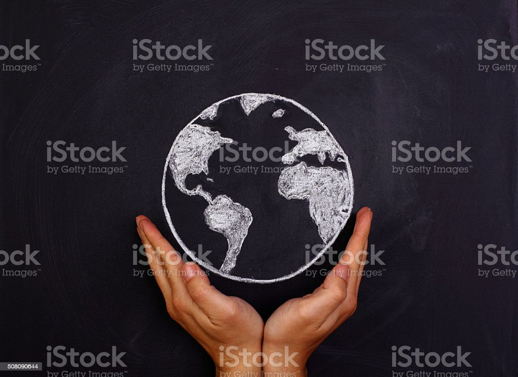Holding earth front of black blackboard stock photo