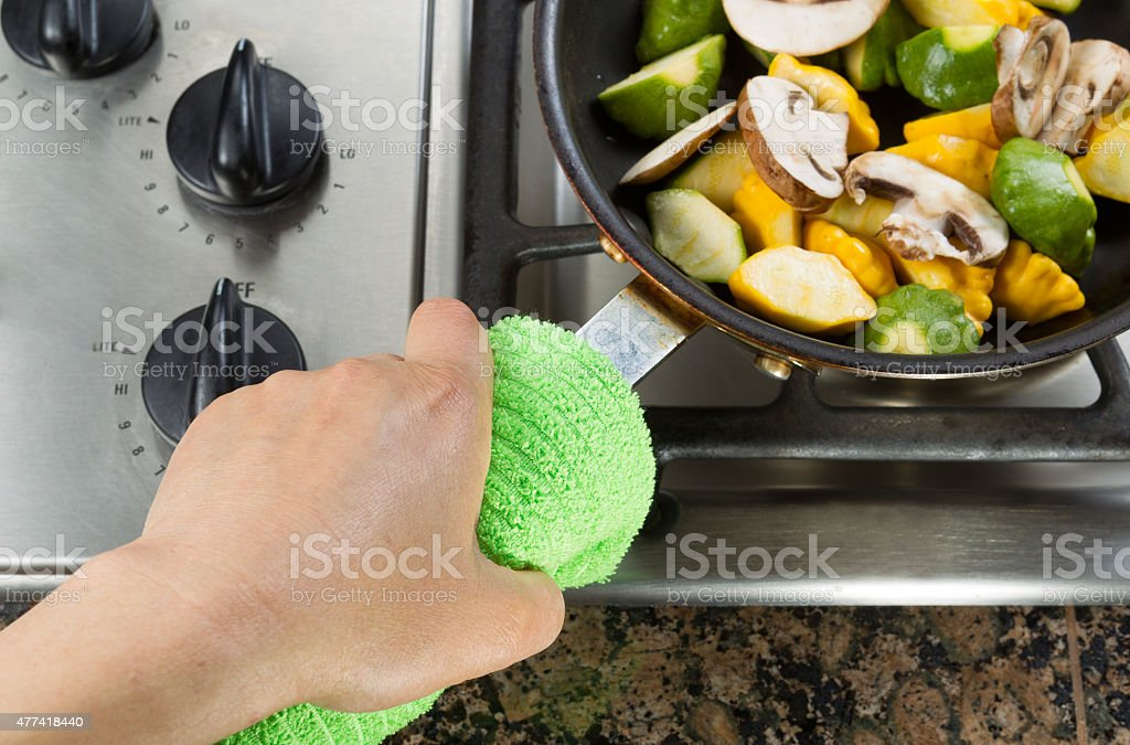 Holding frying pan with green cloth stock photo