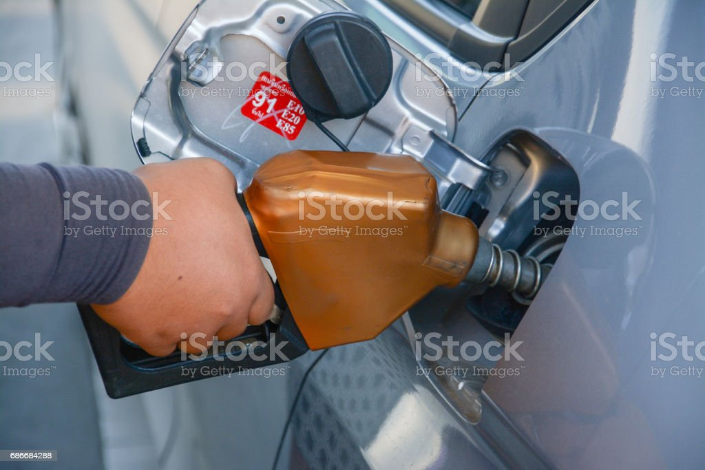 holding fuel nozzle and refuel car  in gas station stock photo