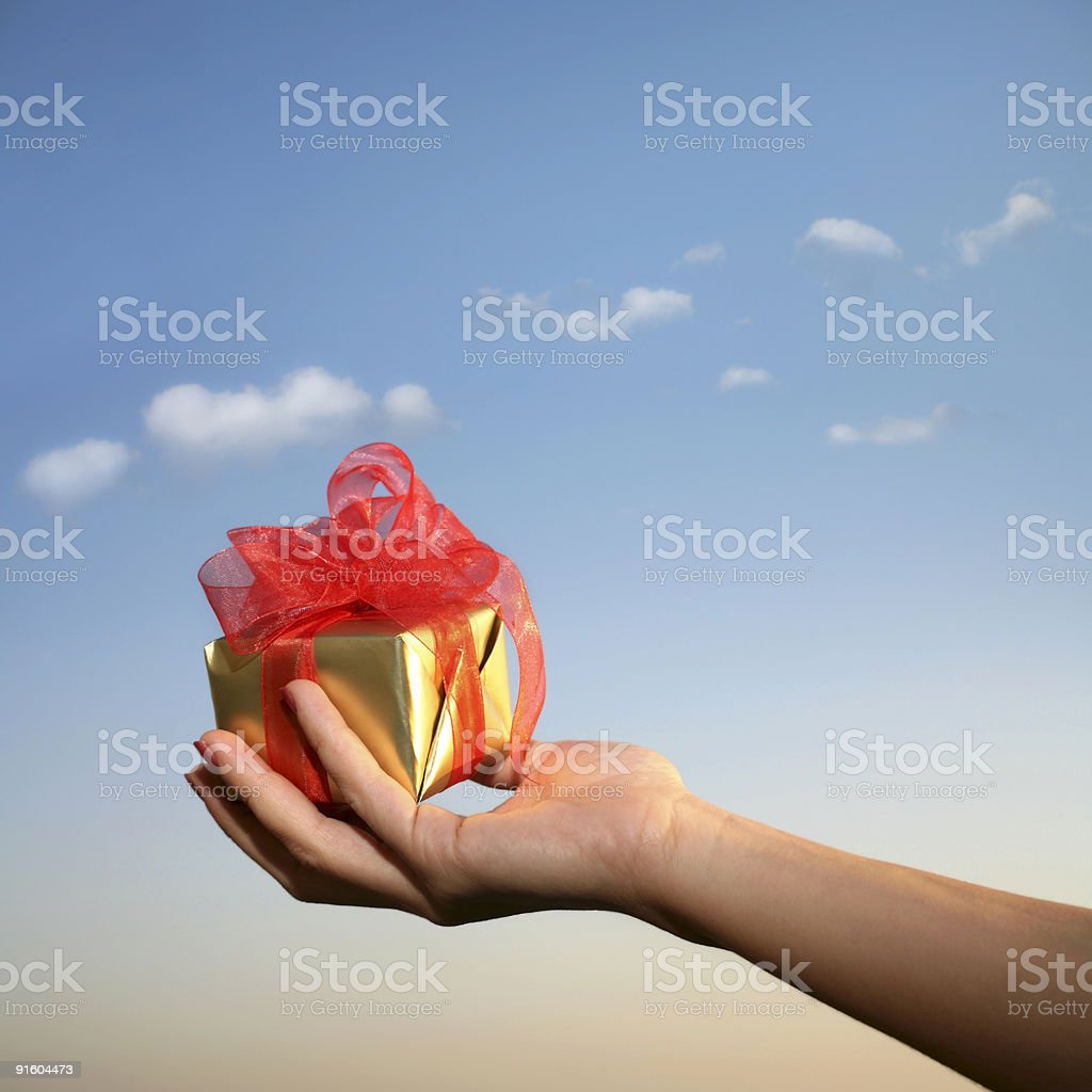 holding gift box over sky royalty-free stock photo