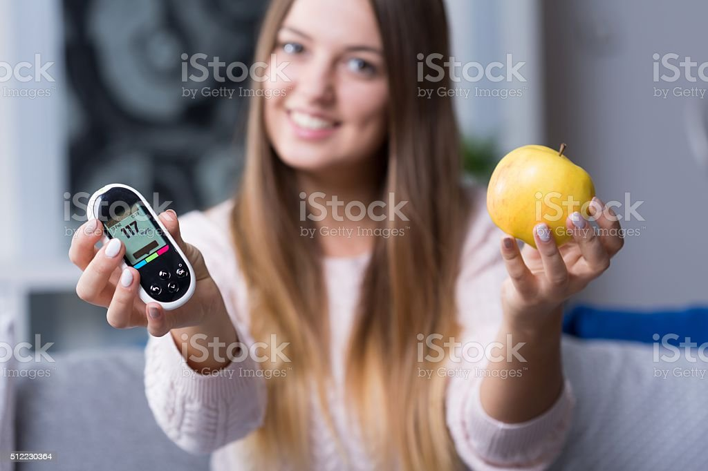 Holding glucometer and apple stock photo