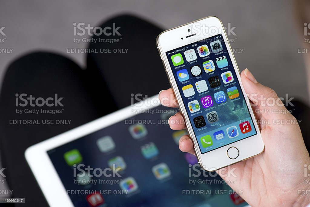 Holding gold iPhone 5S stock photo