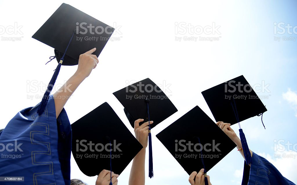 holding graduation hats stock photo