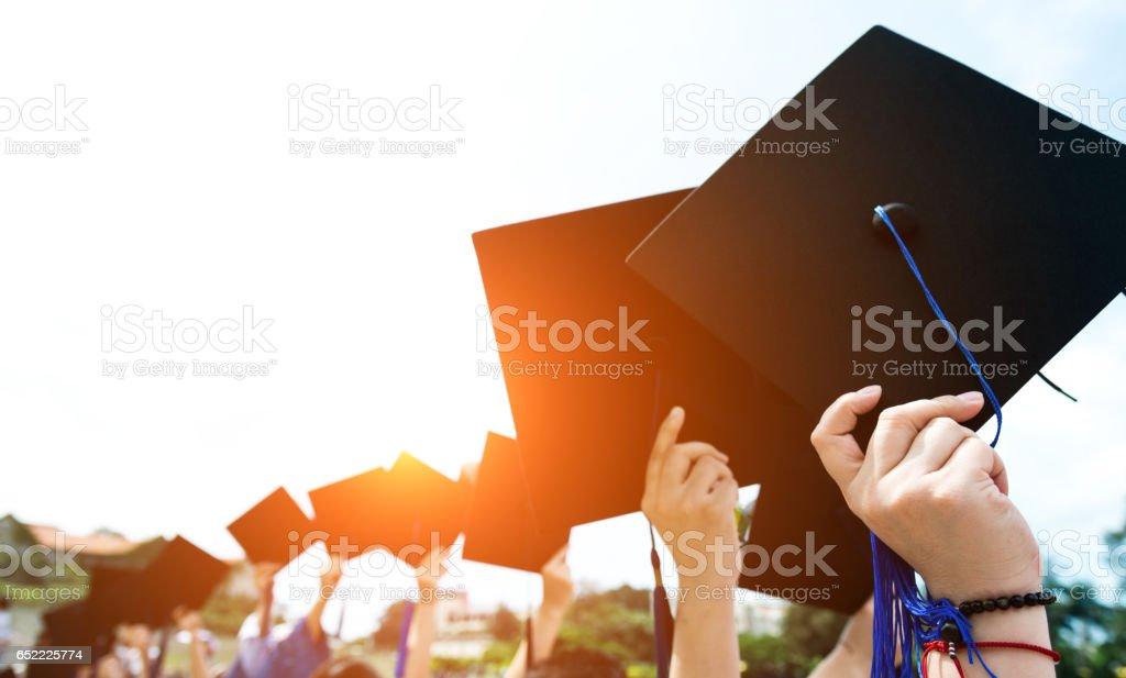 holding graduation hats stock photo