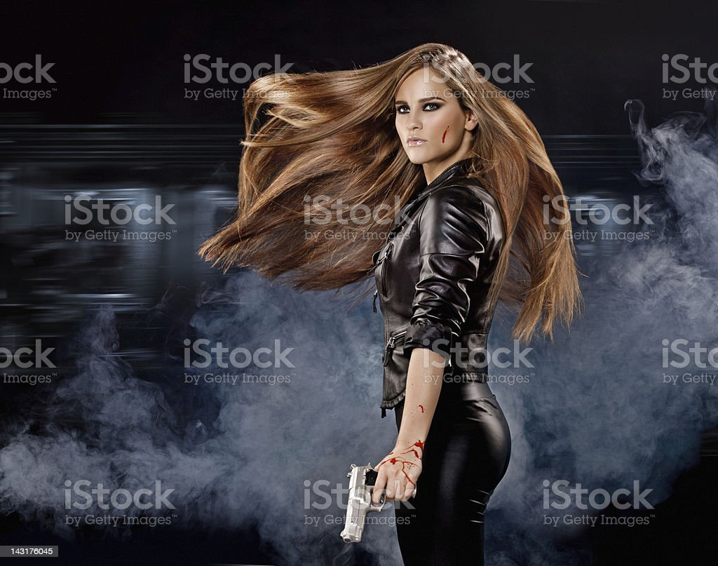 Holding gun sexy woman with long flying hair stock photo