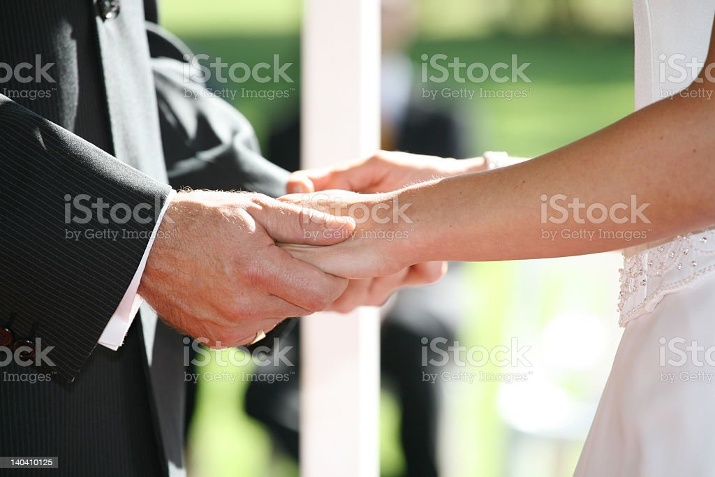 Holding hands close up during wedding ceremony stock photo