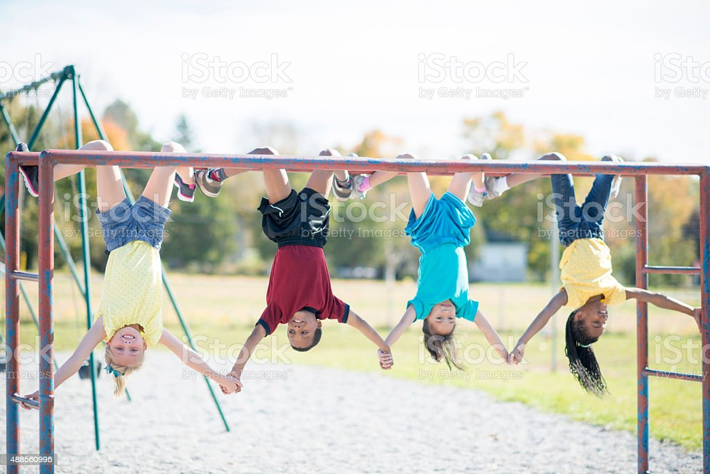 Holding Hands Upside Down on Monkey Bars stock photo