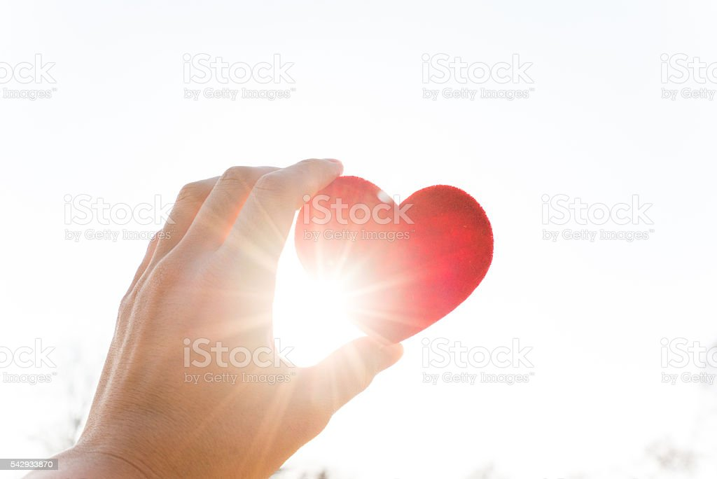 Holding heart under the sun stock photo