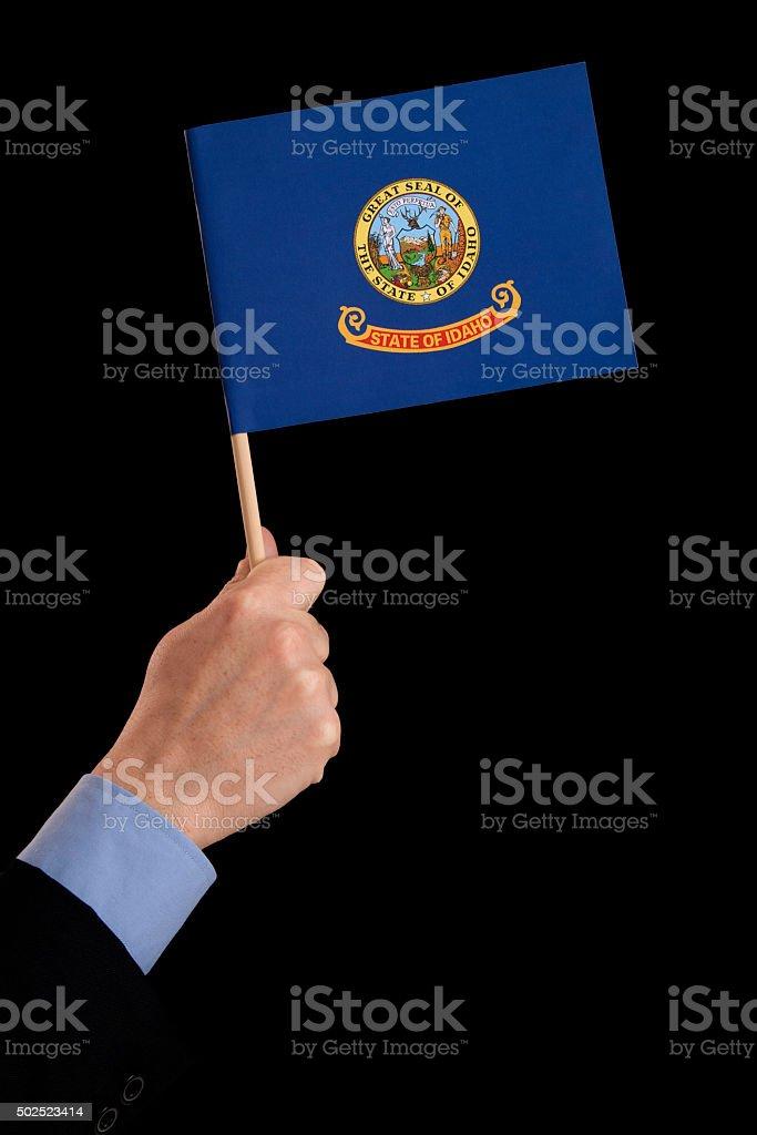 Holding Idaho flag stock photo