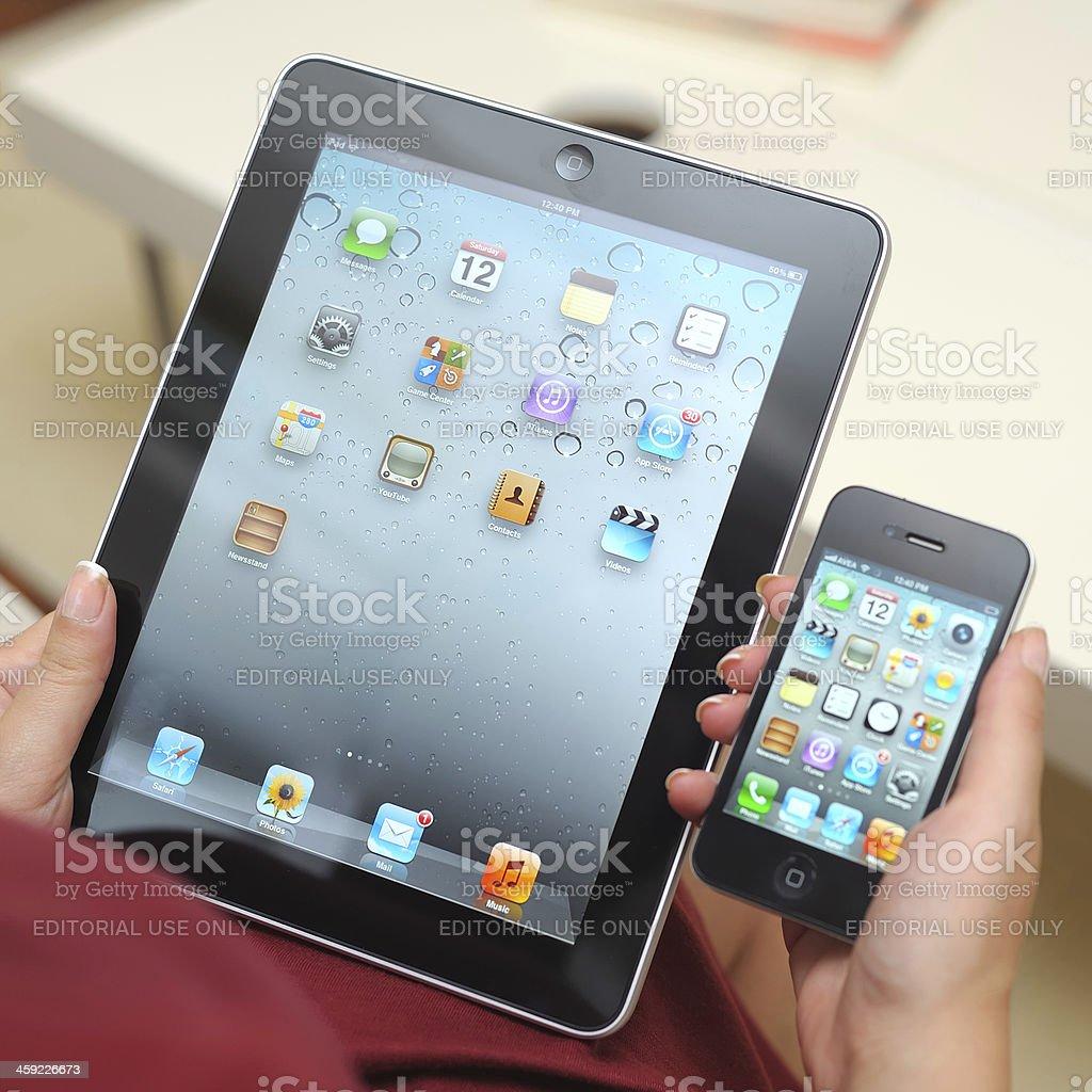 Holding iPad and iPhone 4 stock photo