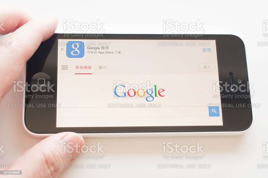 Holding iphone for google search engine stock photo