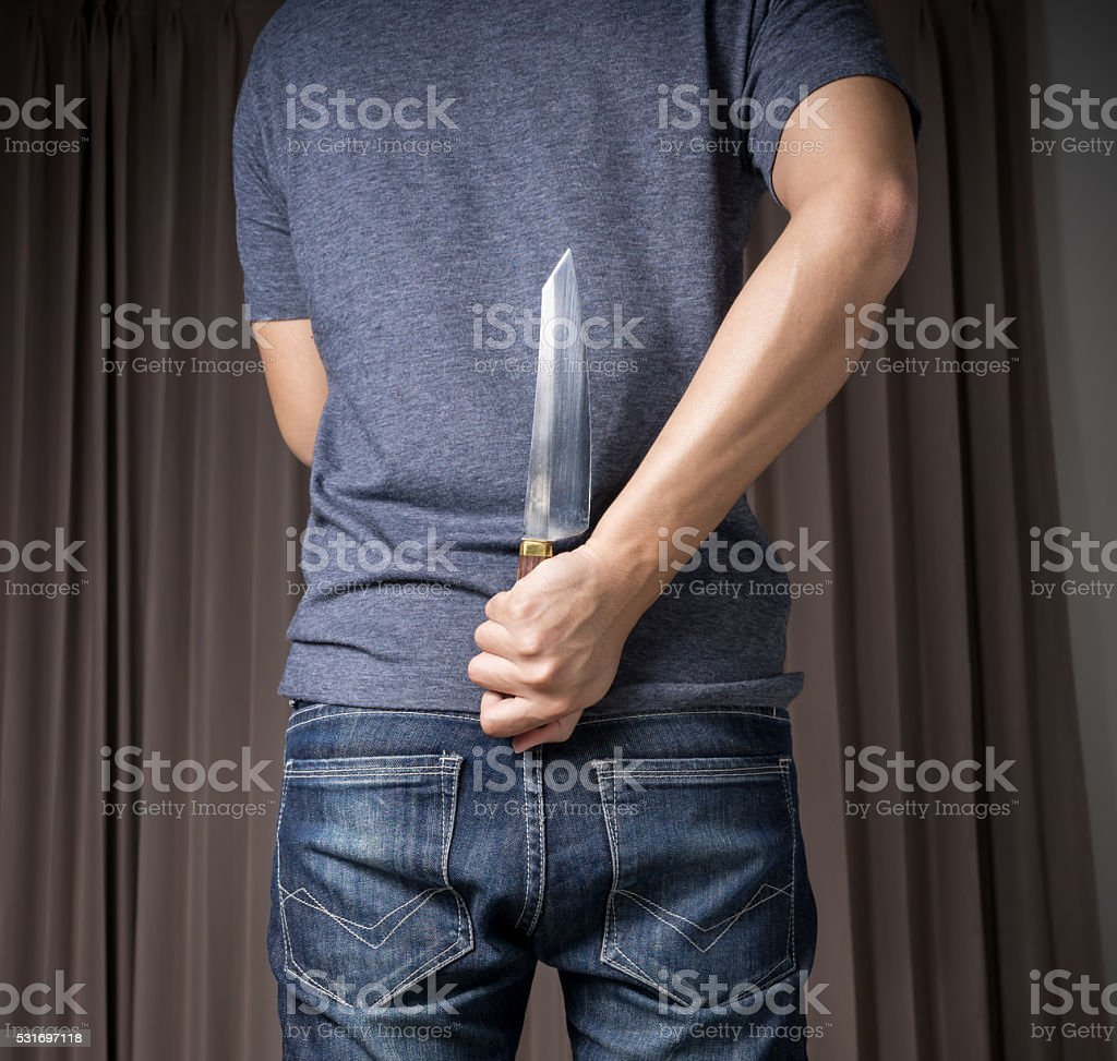 Holding Knife Behind His Back stock photo